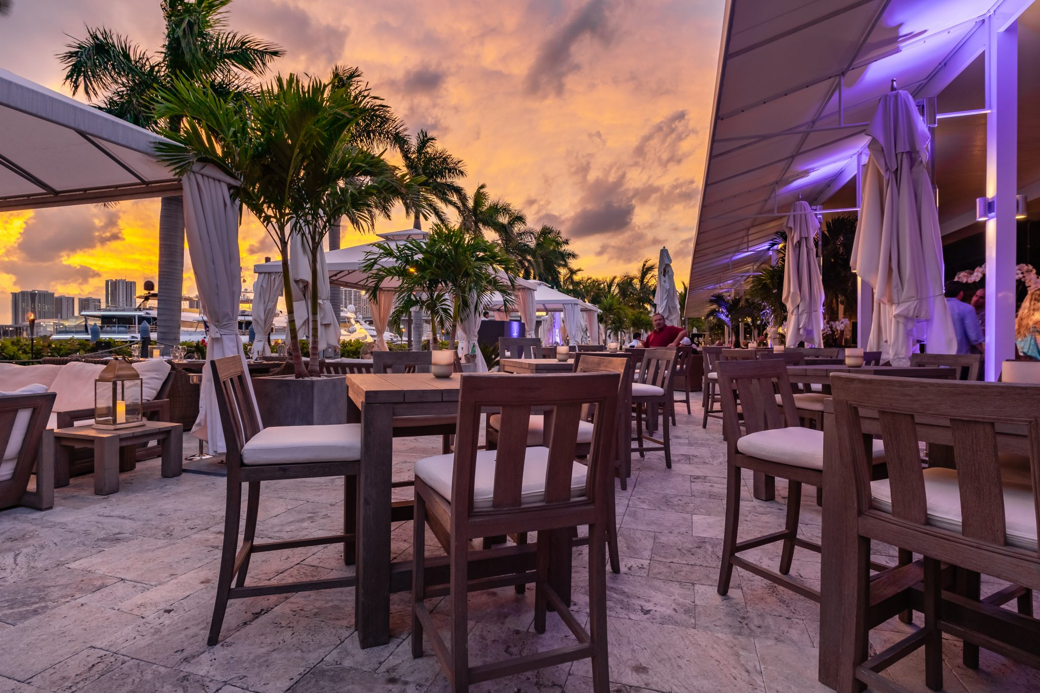 sunset sky at marina as backdrop to high top tables