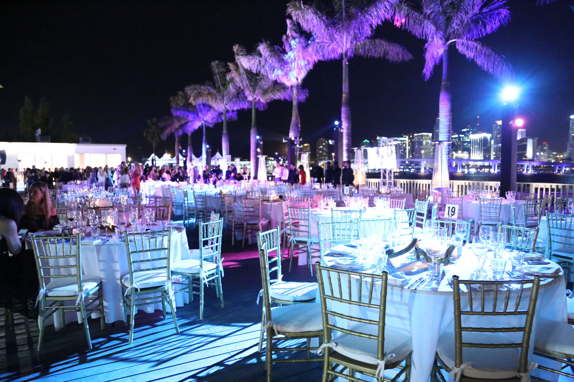 photo of tables outside by palm trees at night